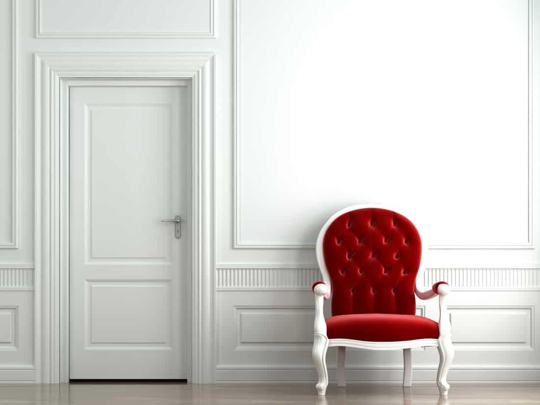Red velvet accent chairr against white wall
