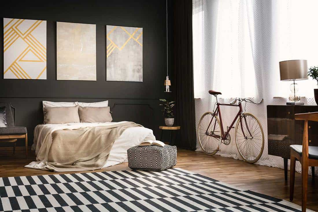 Retro bedroom interior with bike, bed, paintings and rug on the floor