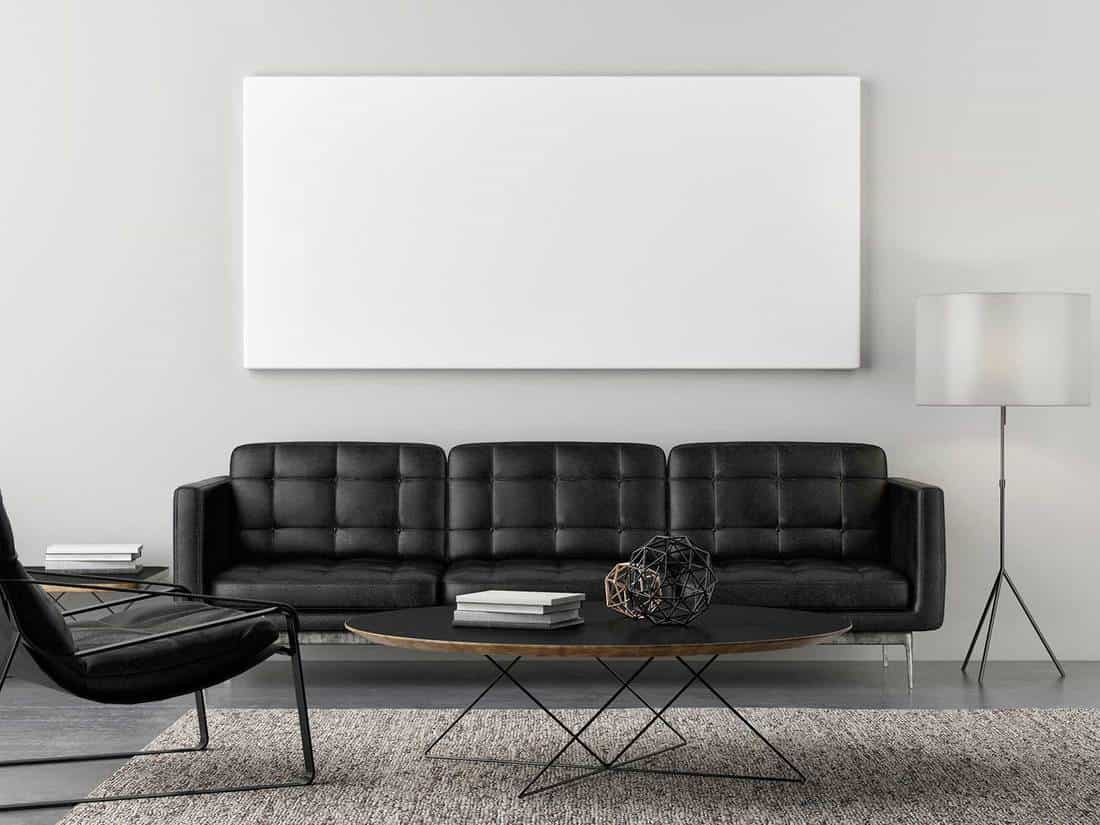 Retro living room with blank poster and black sofa