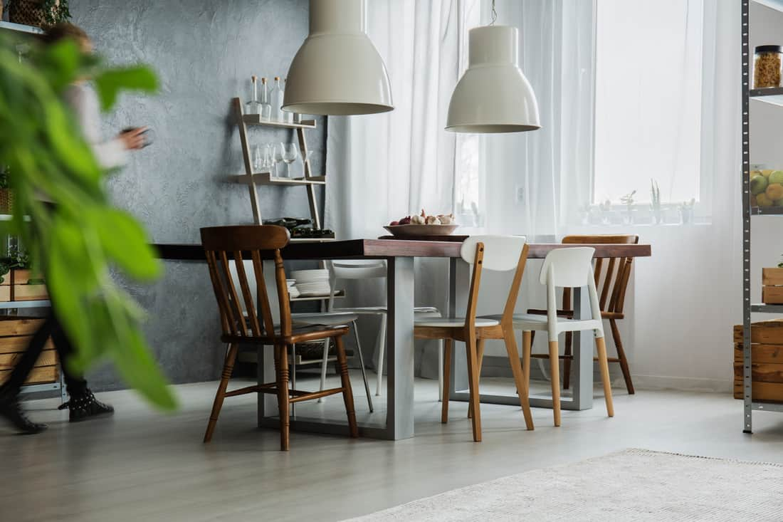 Rustic oak table, different chairs and dark wall in dining room