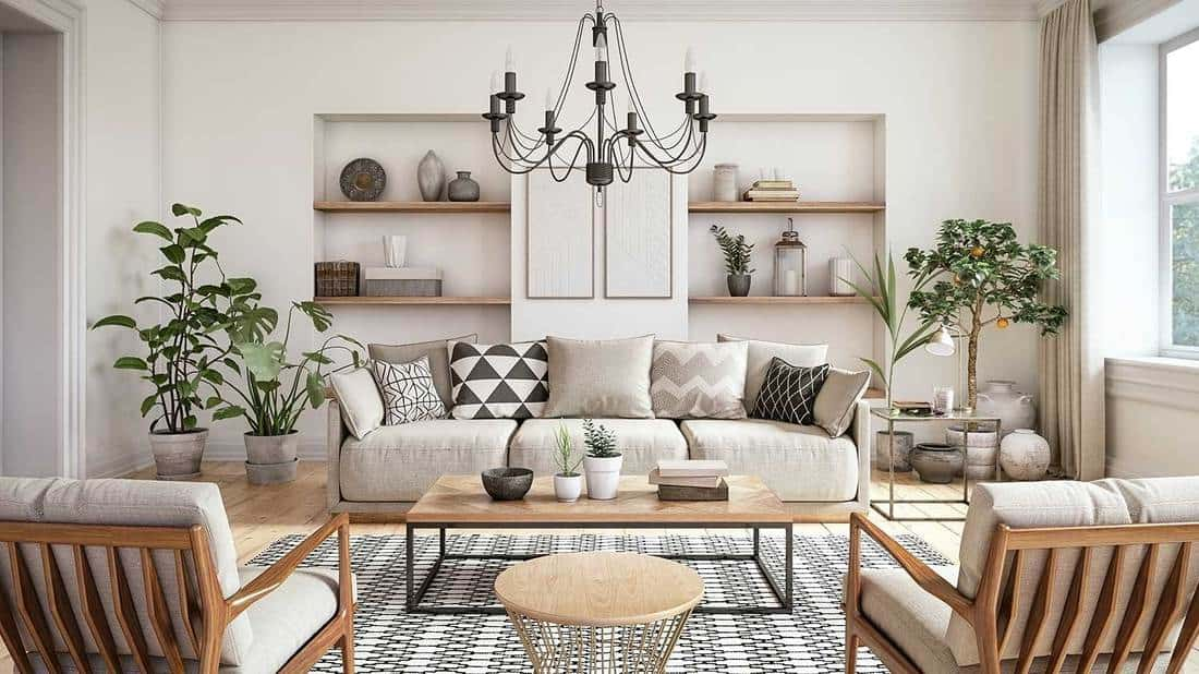 Scandinavian interior design living room with beige colored furniture, house plants and wooden elements