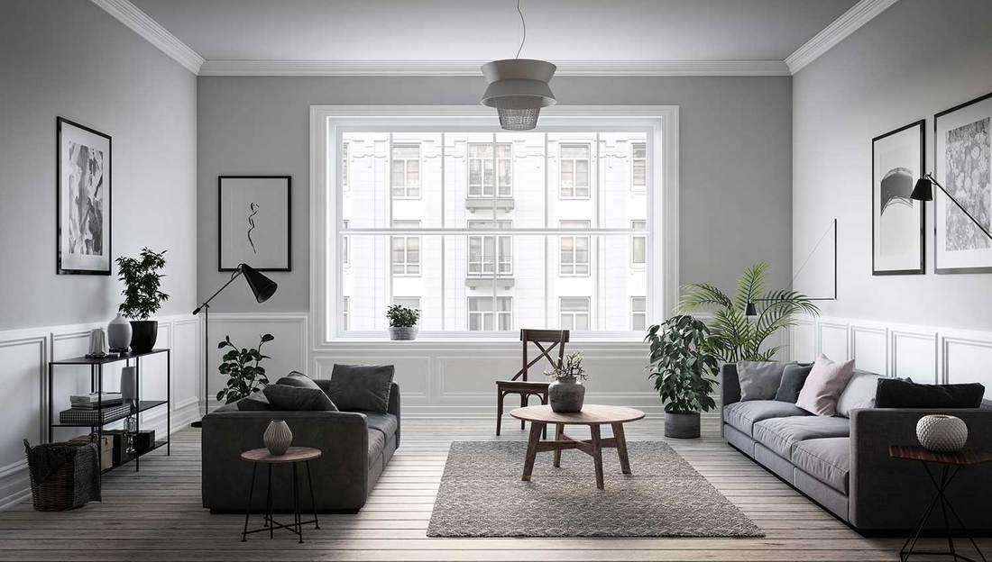 Scandinavian interior design living room with gray sofas, framed artwork on wall and carpet on hardwood floor