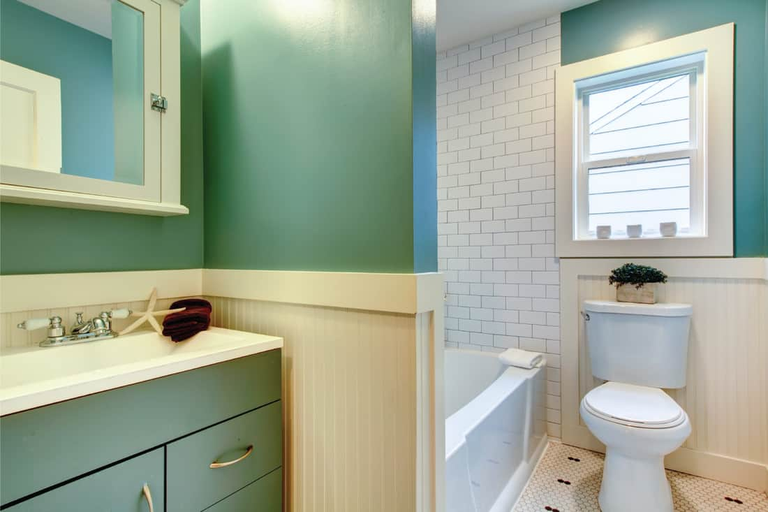 Seafaring Beauty. cruise ship style bathroom with painted wood panels, teal wall, nautical accents