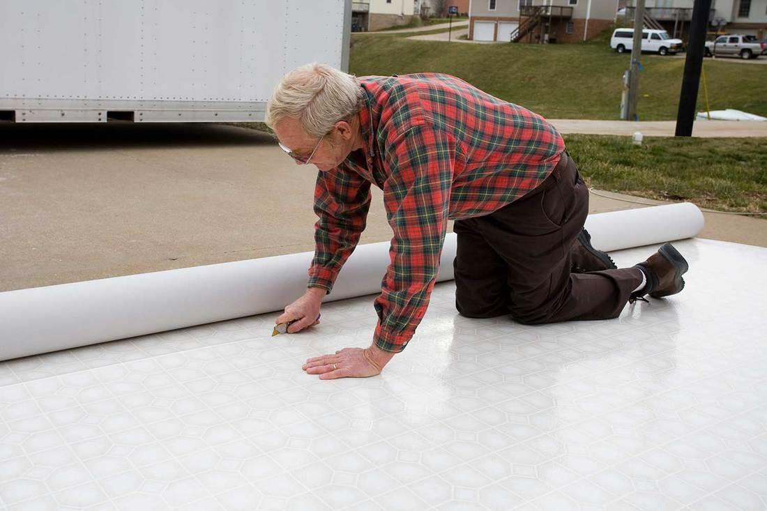Senior person installing vinyl flooring