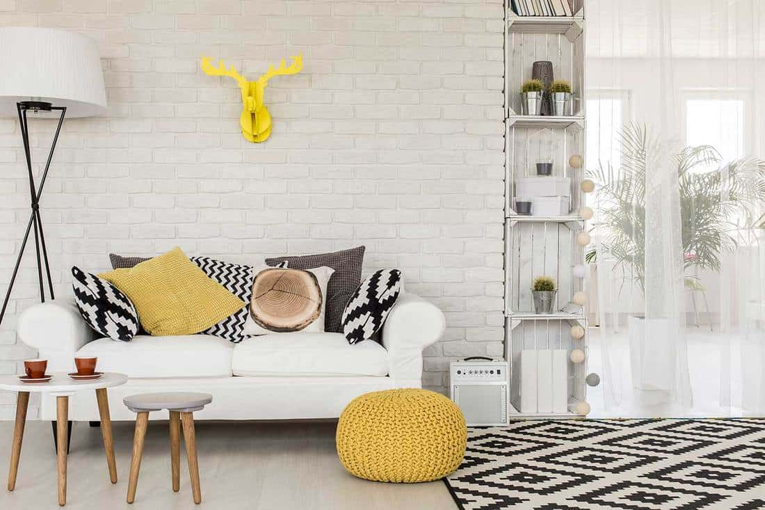 Shot of a sofa in a modern studio living room with white sofa and brick wall
