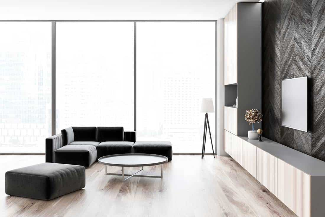 Side view of loft living room with wooden floor and black wooden walls, a sofa and a round coffee table