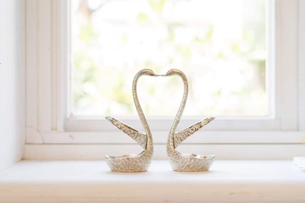 Silver metallic swans on a windowsill