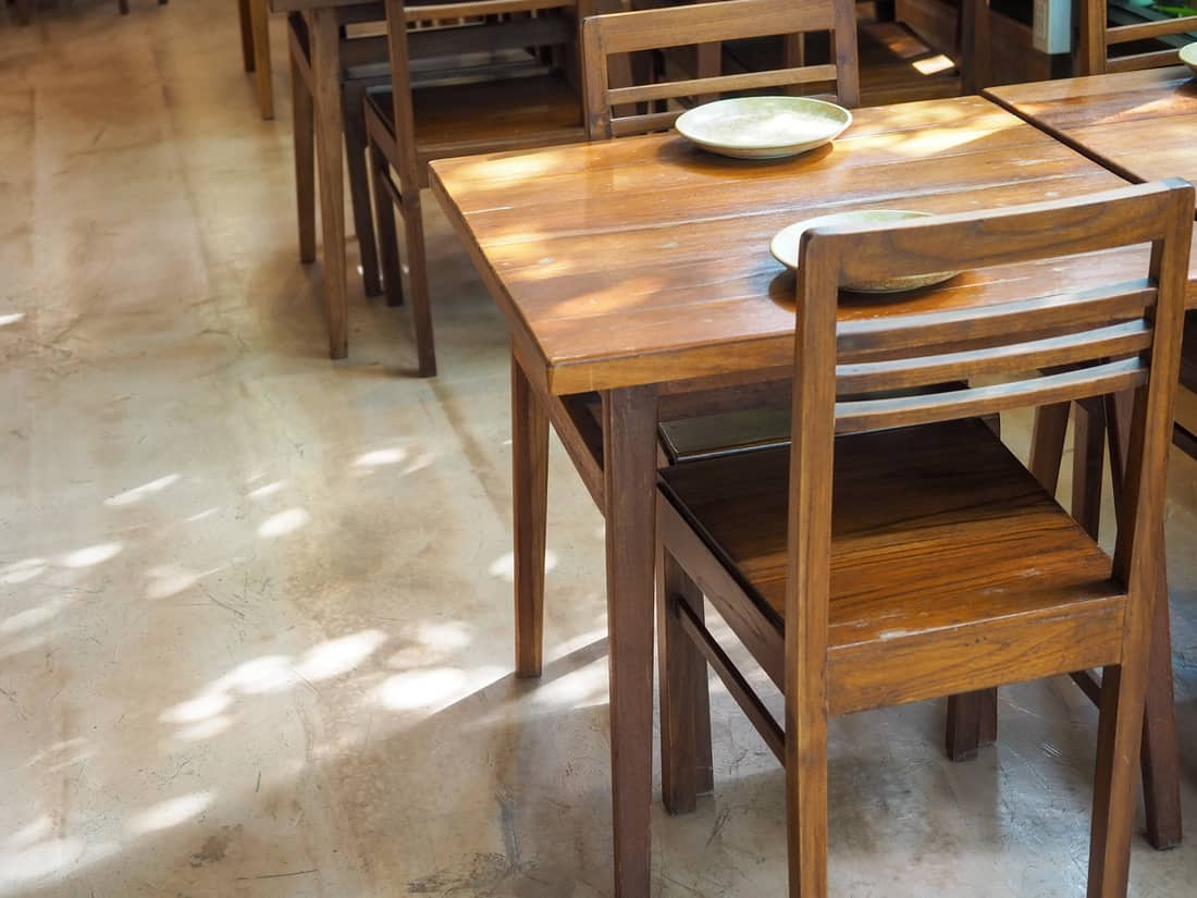 Simple wooden dining table with empty dish and wood chairs with copy space.