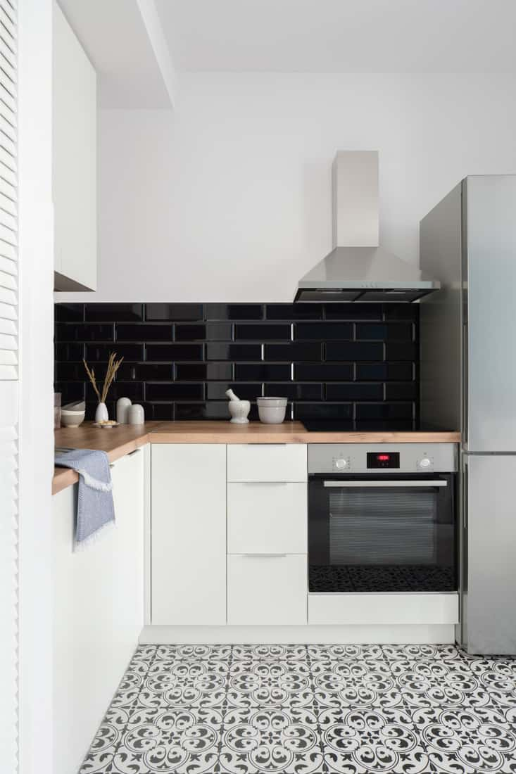 Small kitchen with white cupboards, drawers and wardrobe, silver fridge, oven and exhaust hood and wooden countertop. black patterned tiles on floor