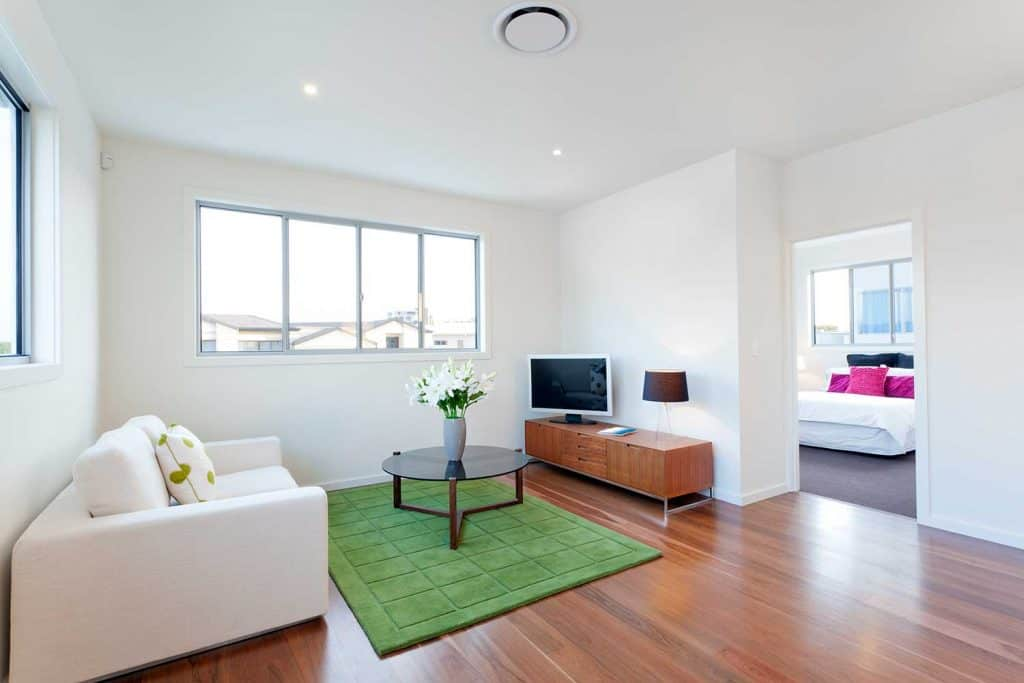 Small modern living room with table on green carpet rug, white leather sofa, parquet floor and view of the bedroom
