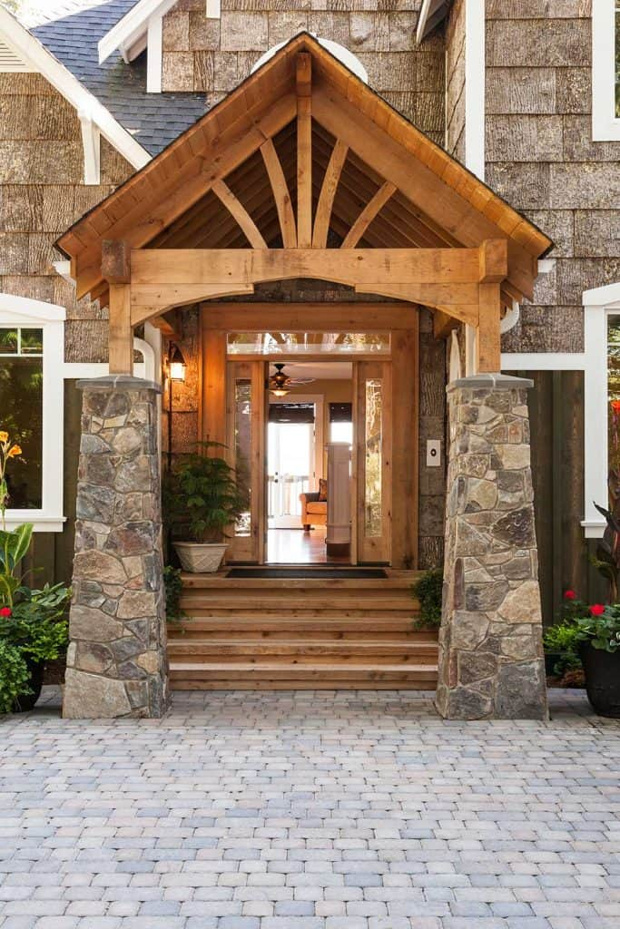 Stone and wood front porch entryway to upscale country house with open front door and paving stone driveway