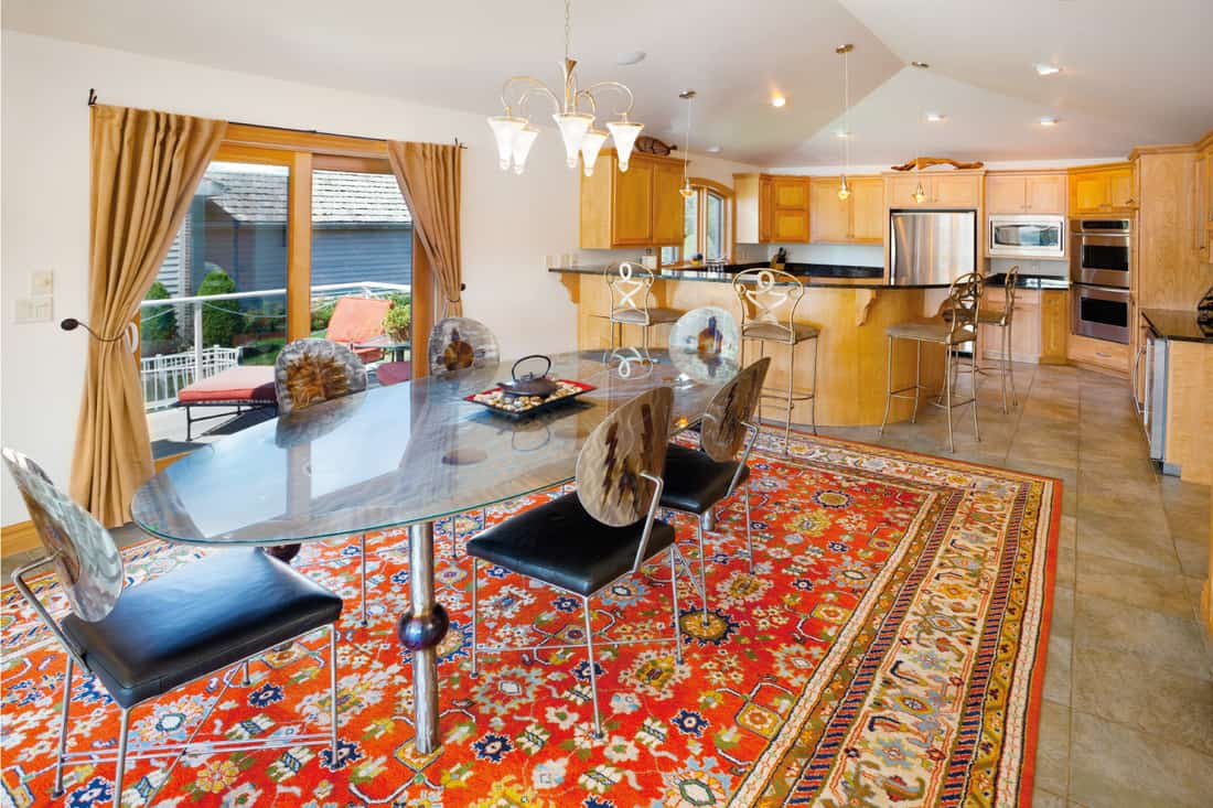 Stylish Dining Room With Adjoining Kitchen. contrasting red color of carpet for flooring. maple cabinets in the kitchen