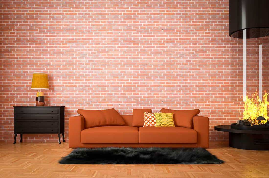 Stylish and cozy living room interior with sofa, table lamp and modern cylindrical fireplace