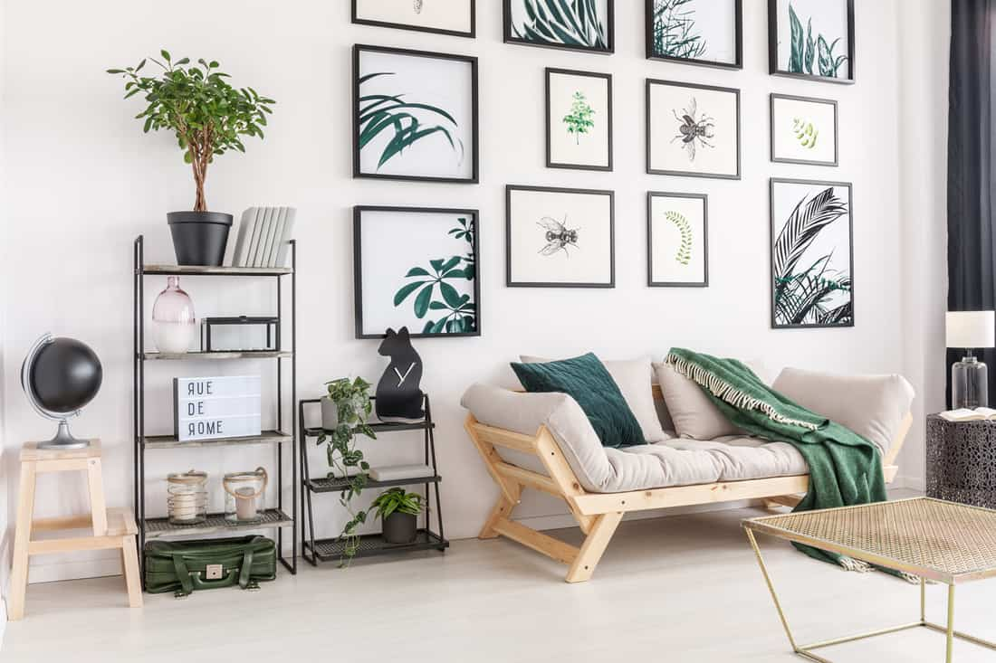 Stylish gallery themed day room with sofa, stack of paintings above the sofa