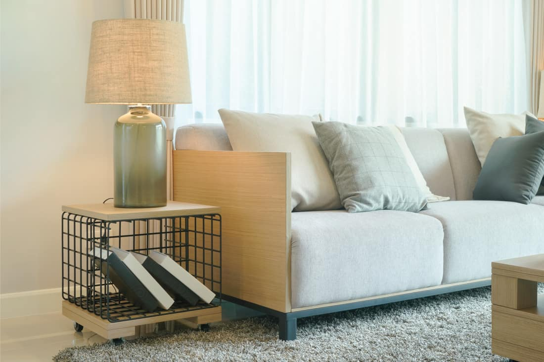 Table lamp next to comfy white sofa in modern style living room with gray carpet