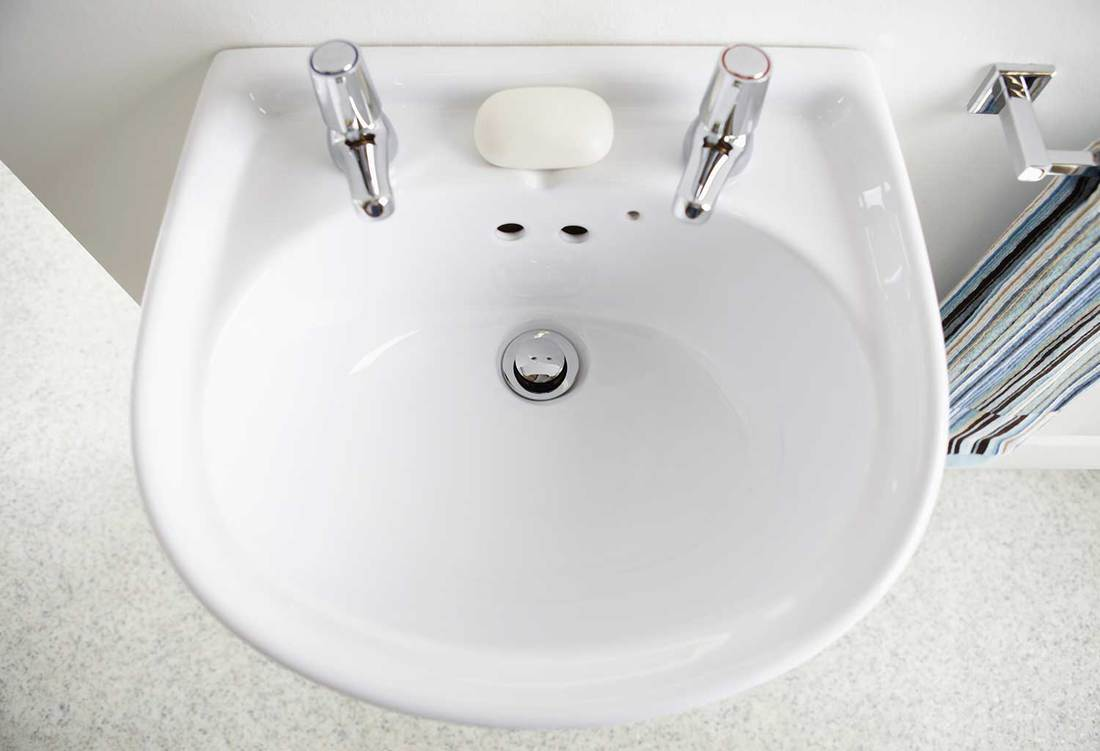 Top view of white sink with two tap in contemporary home bathroom