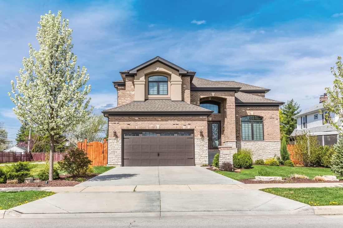 Traditional American Home with Garage door in walnut brown color