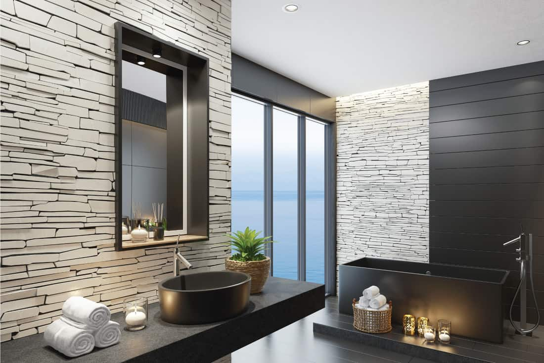 Trendy and modern home spa bathroom with matte black tiles, white stacked stone wall and lots of natural light