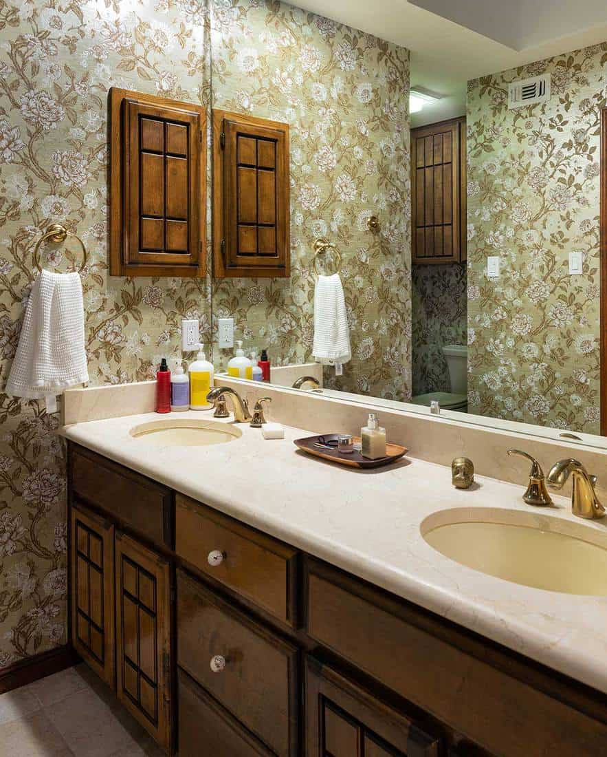 Vintage style master bathroom with old fashioned wall paper design, gold trimmed faucet and pink marble bathtub