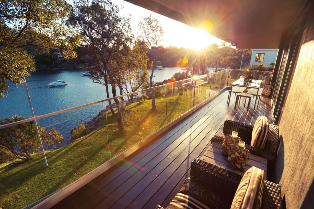 Waterfront house balcony at sunset with wood deck and glass panels on railings