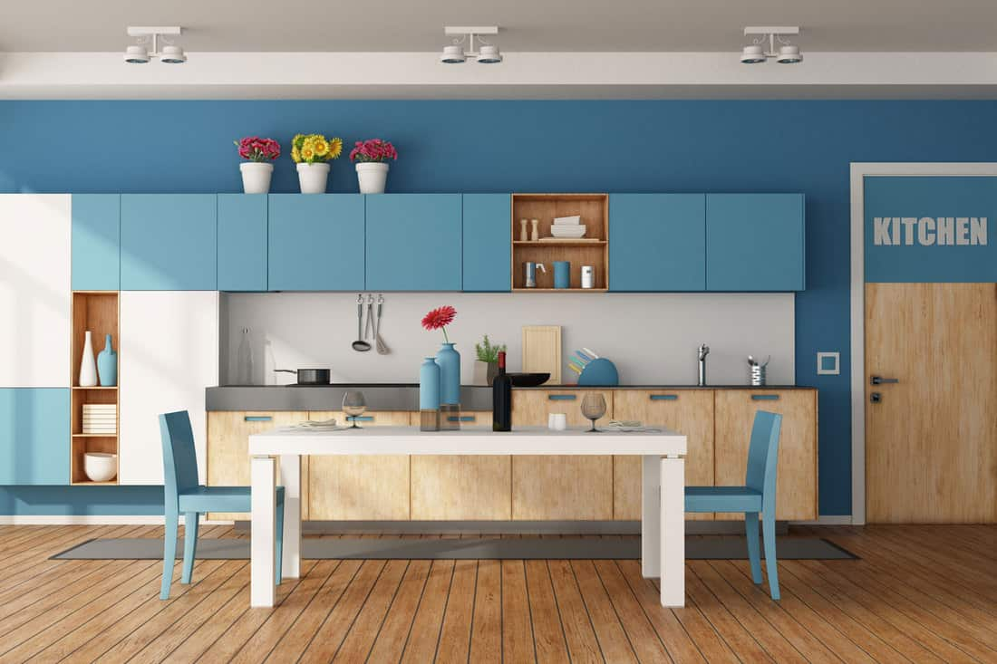White and blue modern kitchen with dining table and closed door