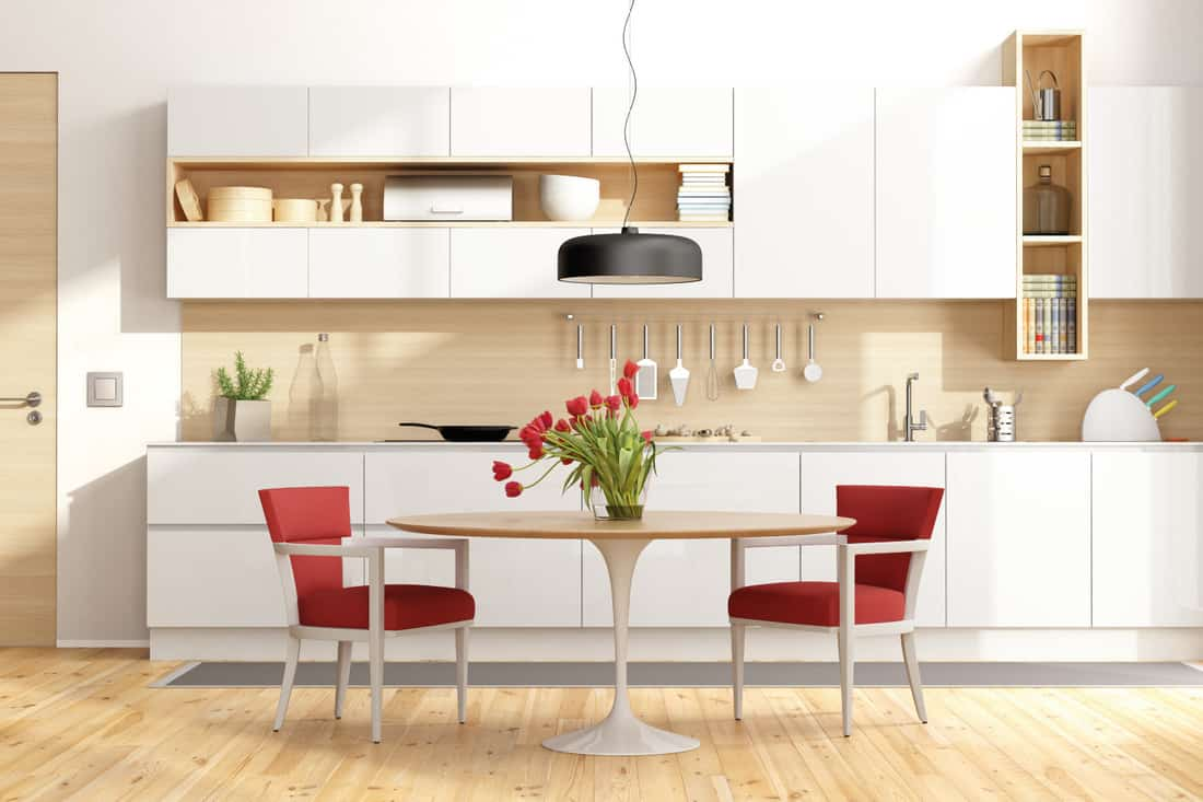 White and wooden modern kitchen with round dining table and red chairs