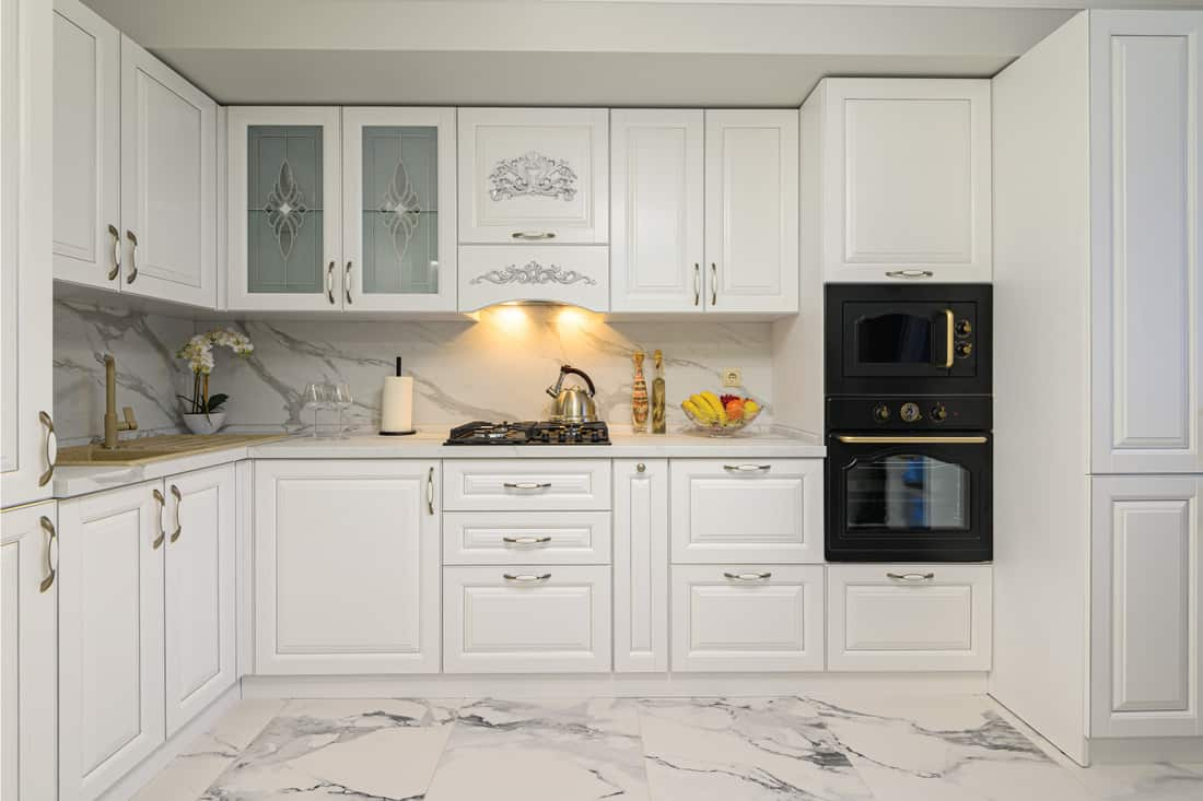 White cozy modern classic kitchen interior with wooden furniture,appliances, marble floor