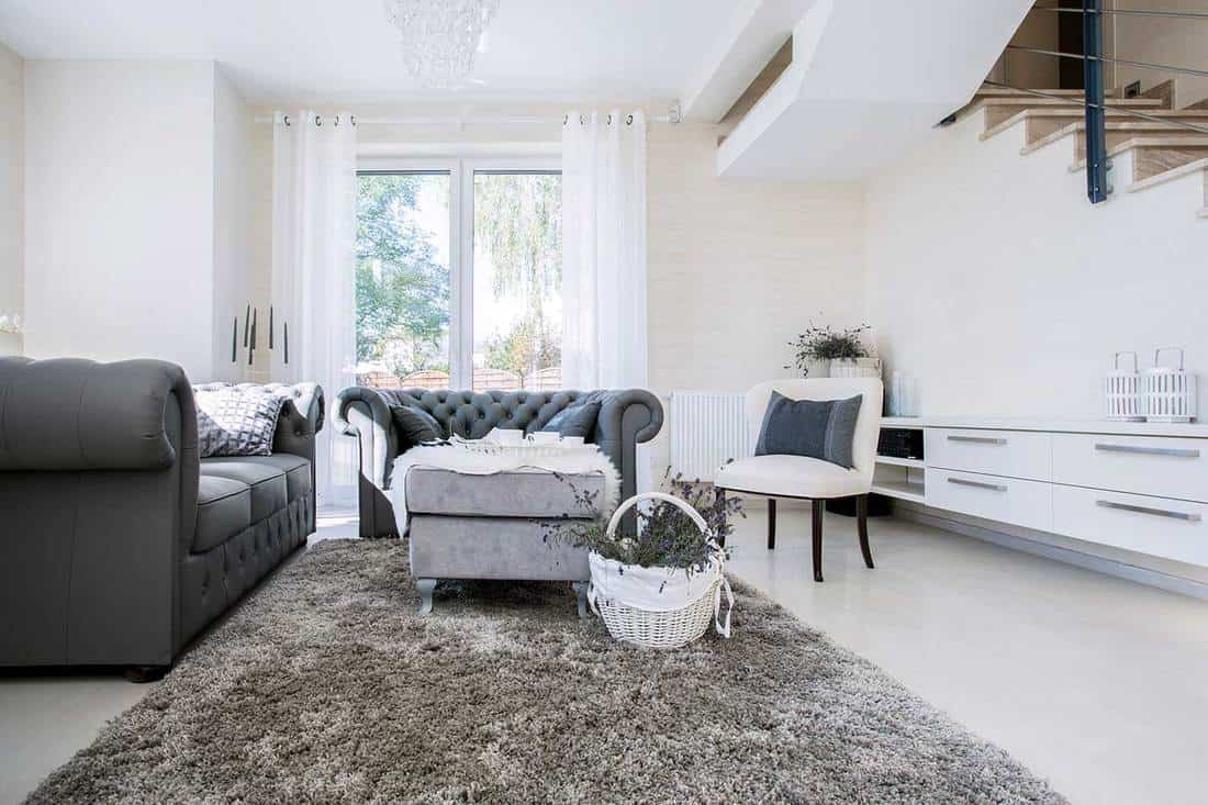 White living room with gray sofa, carpet, white accent chair and white cabinets