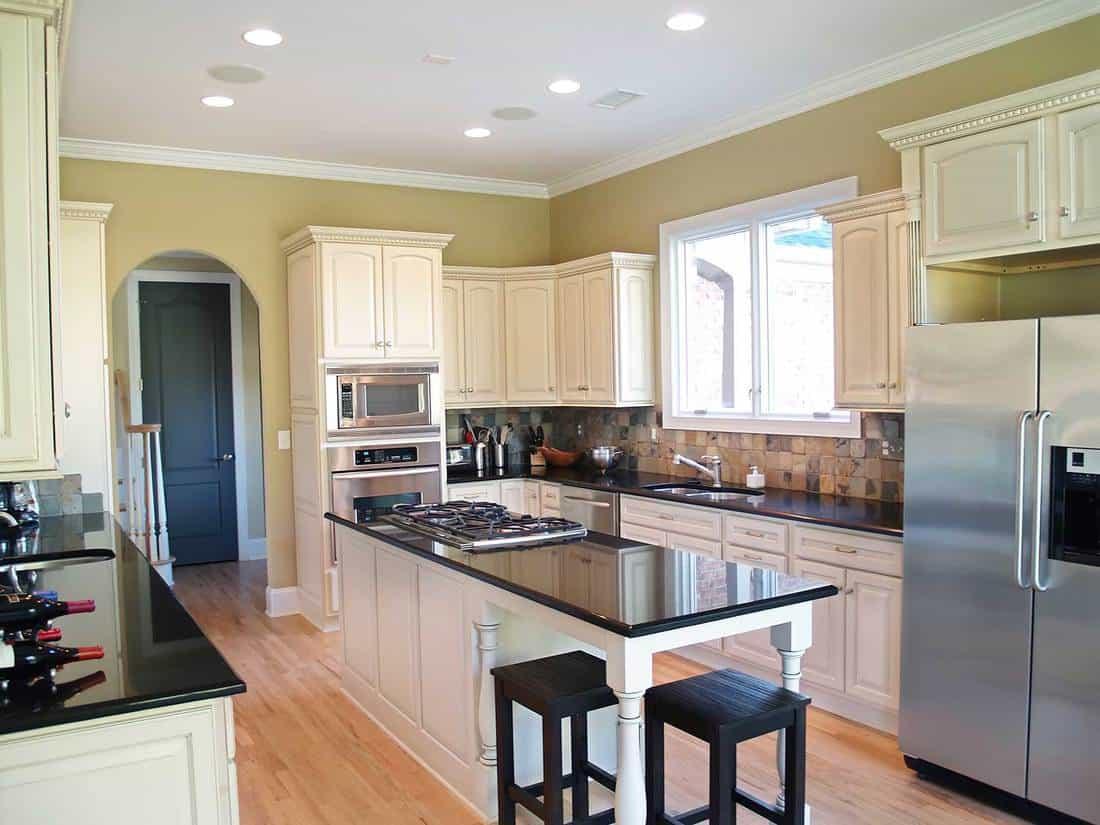 White modern kitchen with island and parquet floors