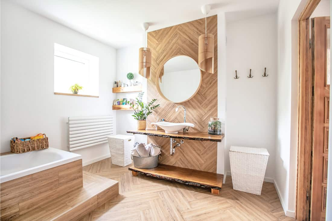 White sink on wood counter with a round mirror hanging above it. Bathroom interior. boho style