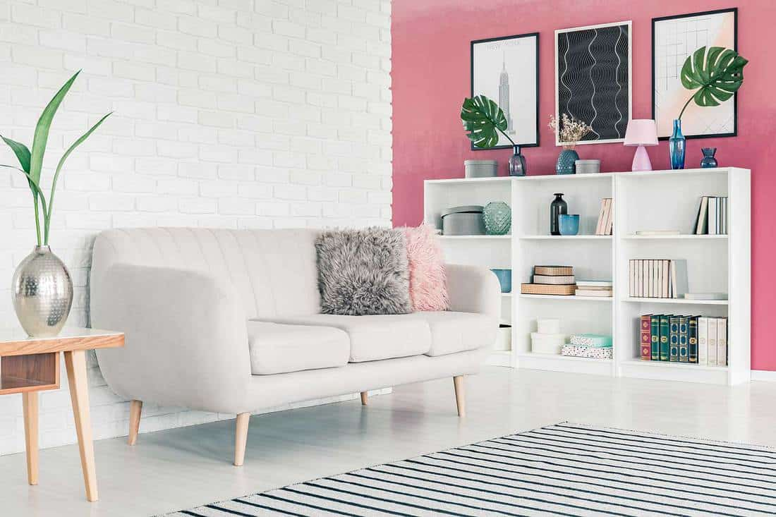 White sofa in pink living room interior with white brick wall, striped rug, posters and bookcase with books and decorations