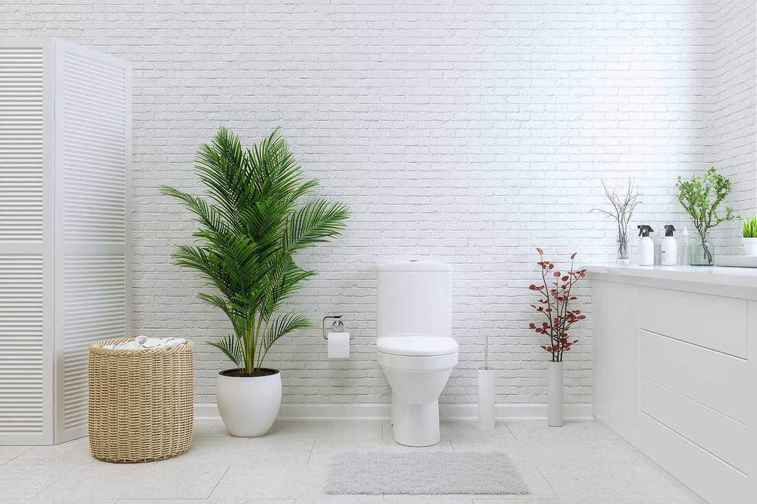 White toilet bowl in a bathroom with brick walls