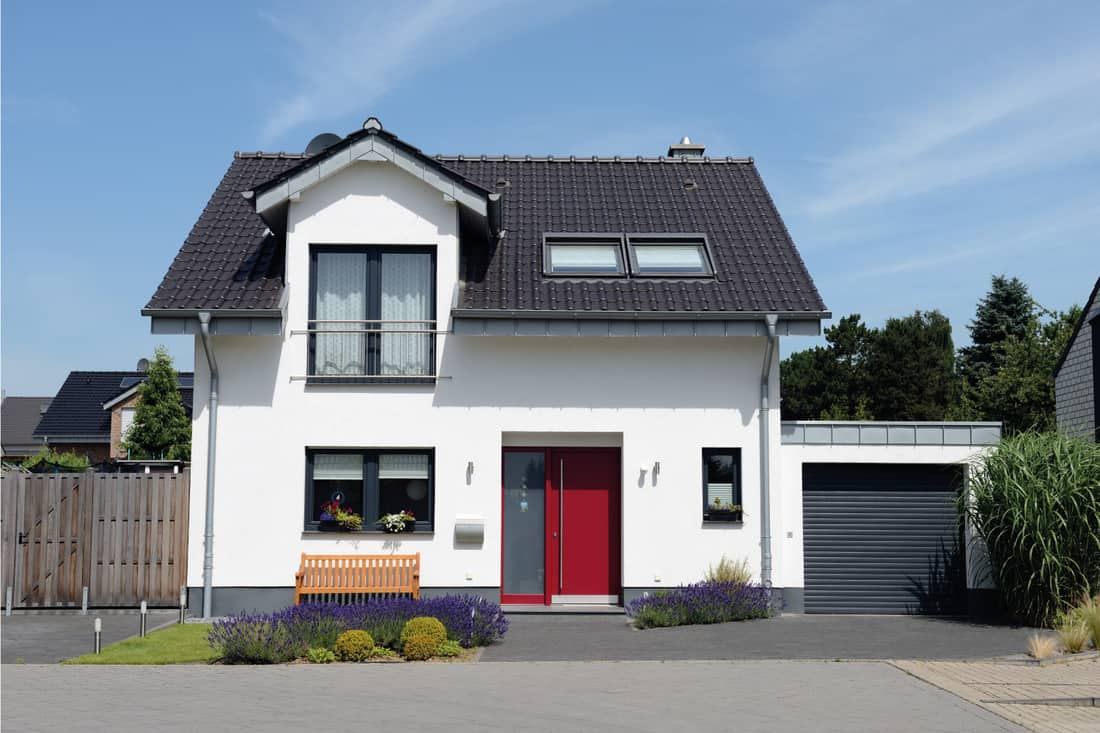 White two-story house with black roof, black garage door and red entrance door