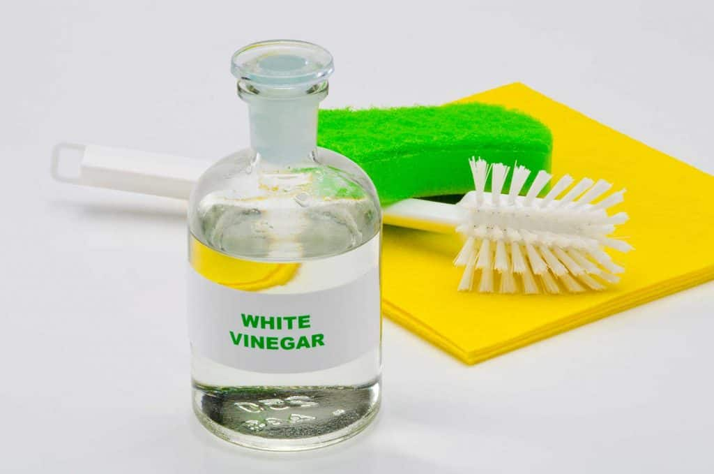 White vinegar in a glass bottle isolated in white background