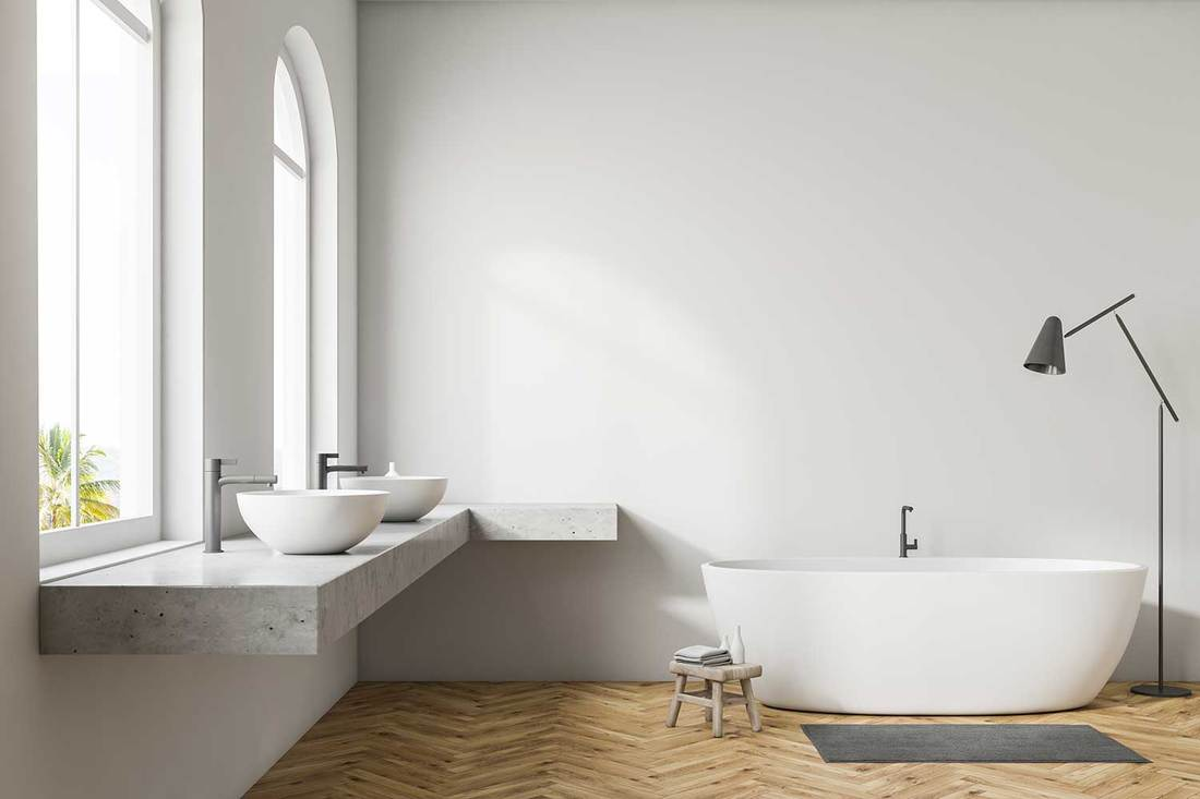 White wall bathroom interior with wooden floor, arched windows, white bathtub and double sink