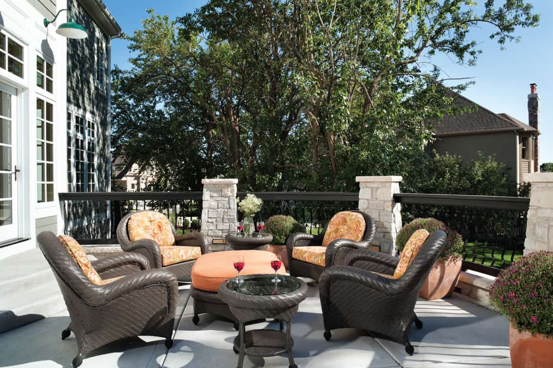 Wicker outdoor furniture decorates a homes lovely outdoor patio with stone and metal railing on a blue sky day.