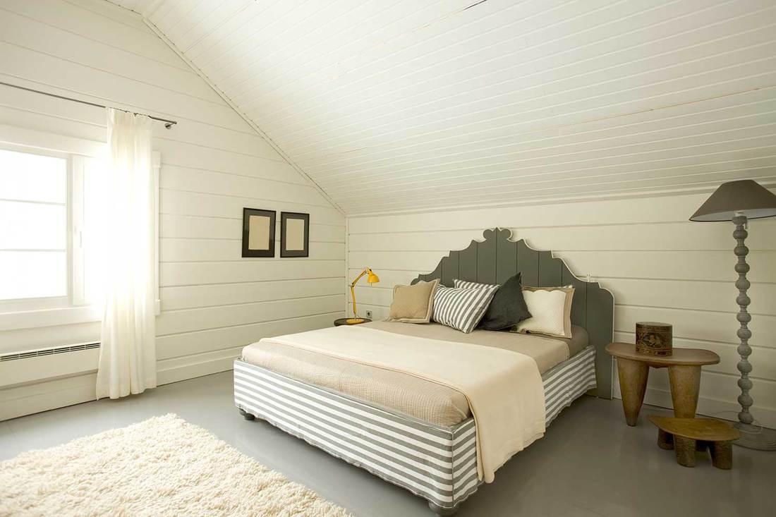 Wide bright bedroom in the attic