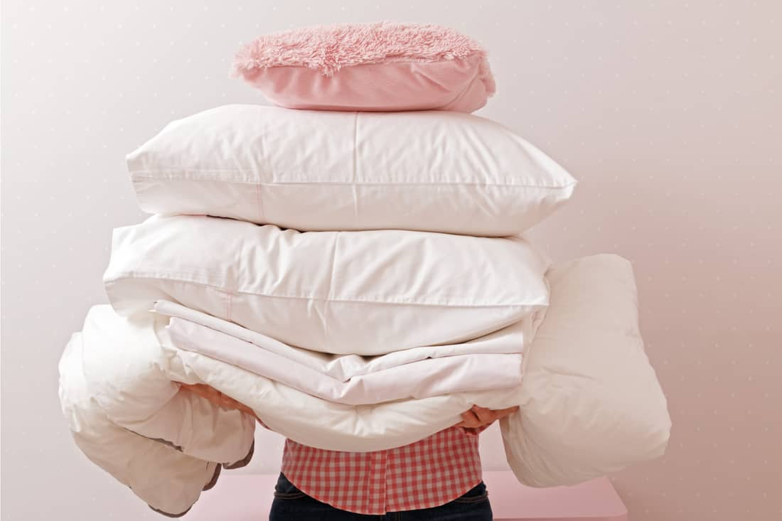 Woman holding a pile of bedding for sleeping