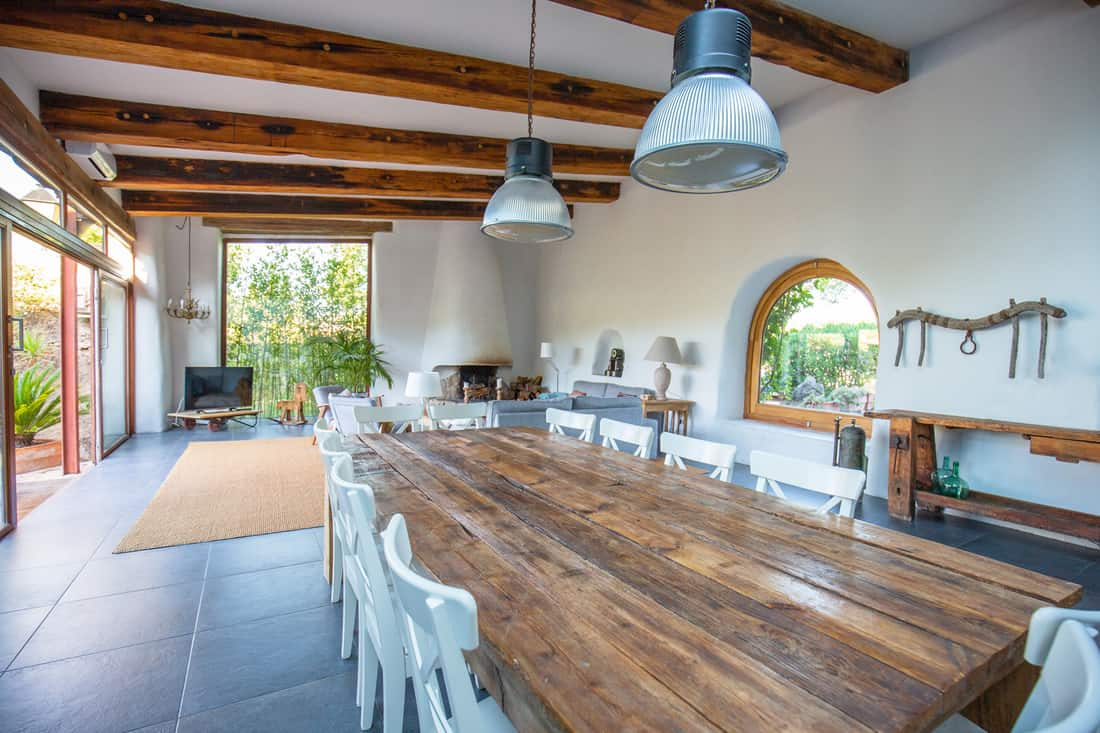 Wood dining table and chairs with living area overlooking garden, Barcelona