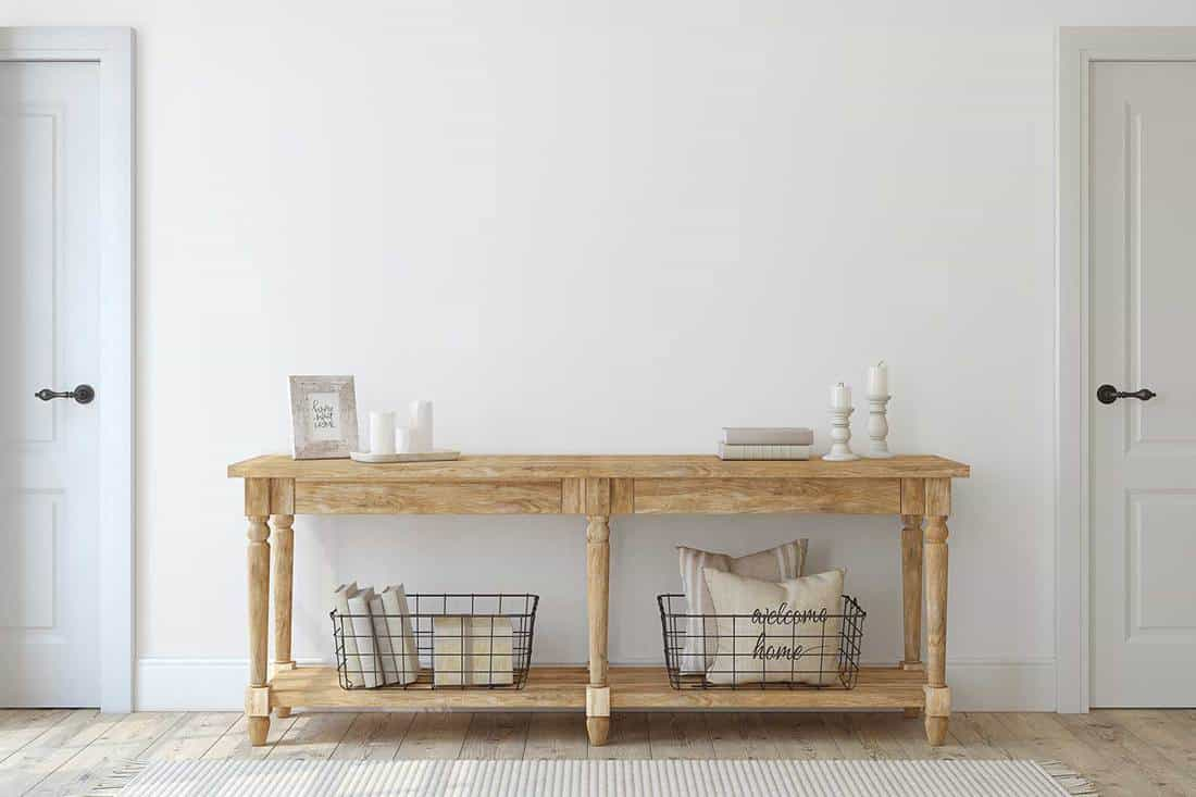 Wooden console table near white wall in farmhouse entryway
