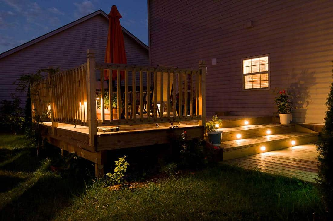 Wooden deck and patio of family home at night