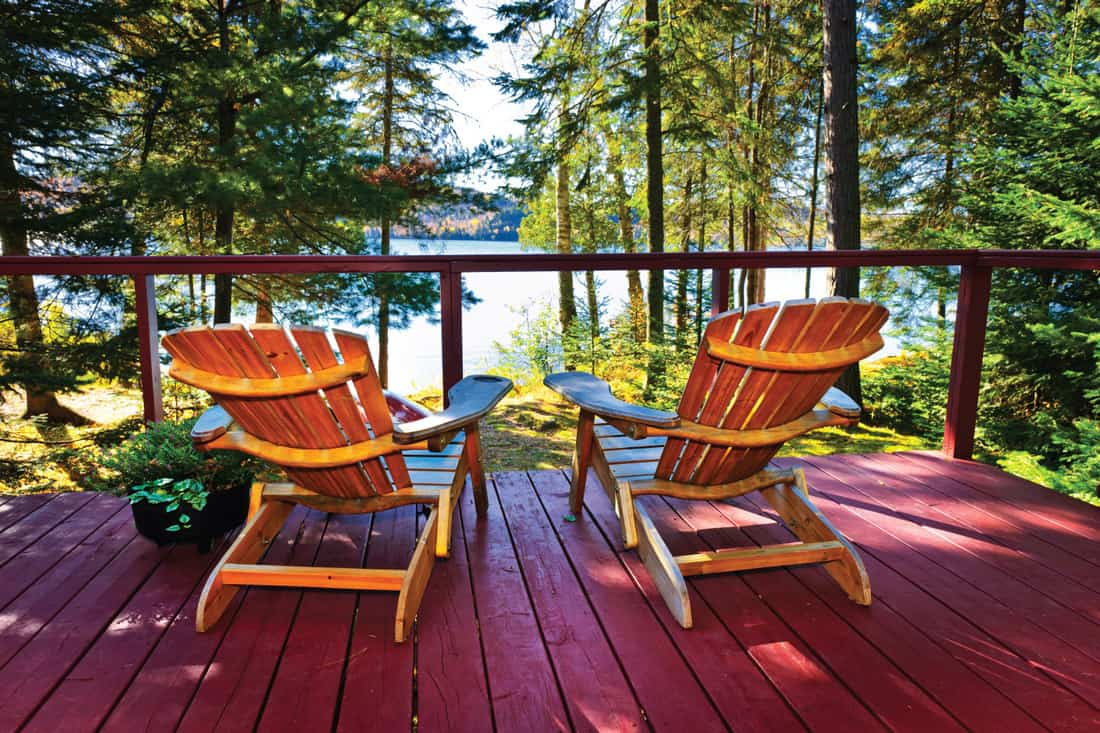 Wooden deck with rustic minimal railing at forest cottage with Adirondack chairs