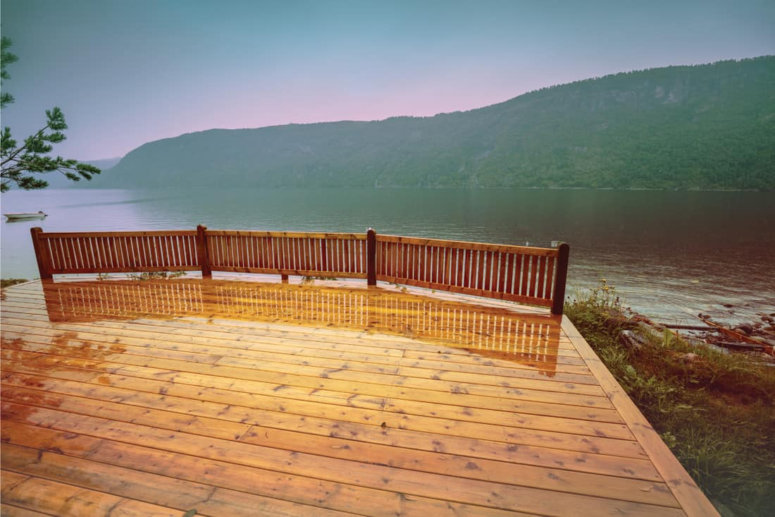 Wooden wet deck with partial wood rail on a lakeshore. Rocky shore of the mountain lake in rainy autumn morning. Beautiful nature