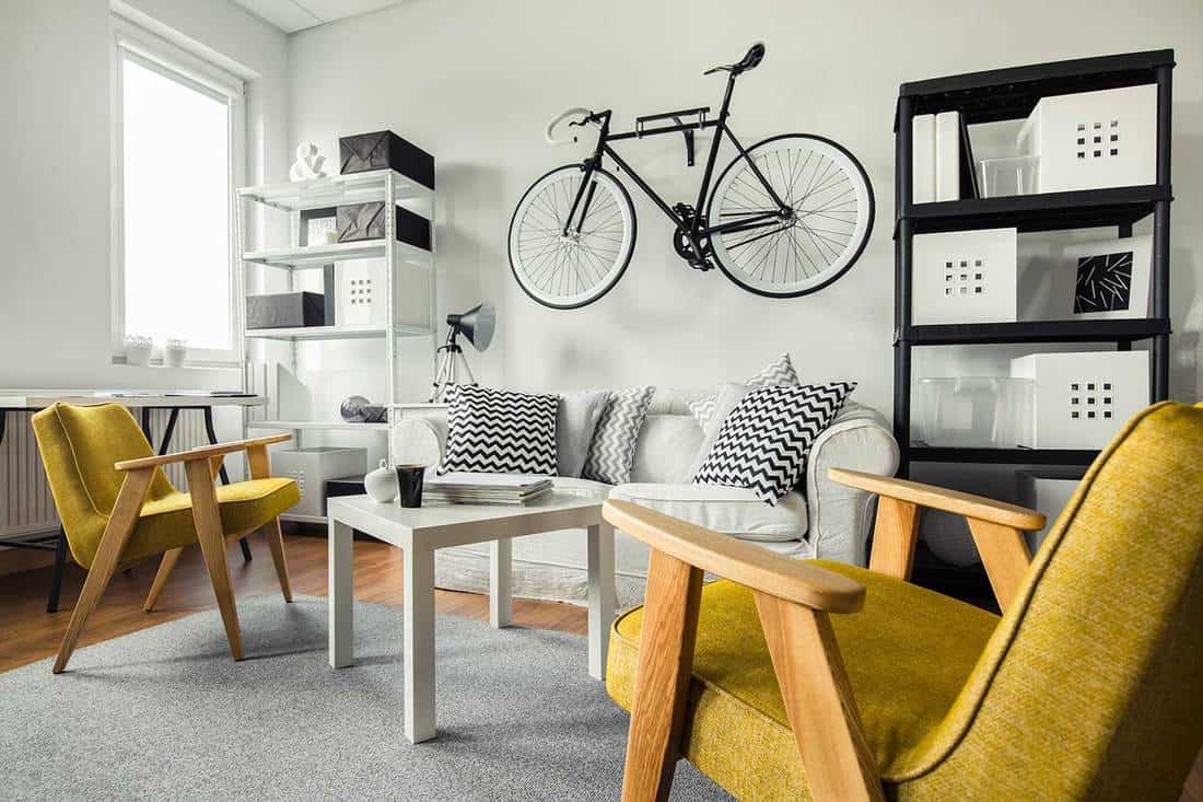 Yellow armchairs in living room with cozy white sofa and bicycle hanged on wall