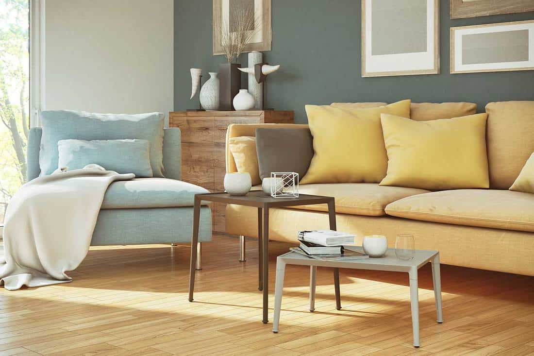 Yellow sofa and blue chair of cozy living room with parquet floor