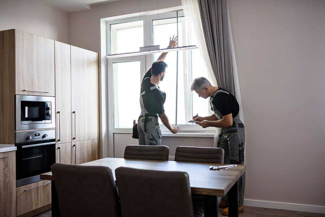 Young professional worker in uniform using tape measure, measuring window for installing blinds, while his aged colleague making notes