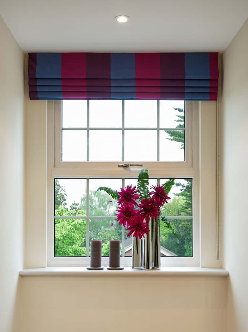 a Geogian style sash window with colourful blinds overhead and complementary red flowers in a modern chrome vase below, next to two brown candles