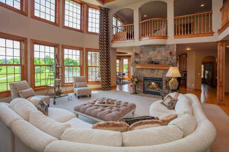 Interior of an amazing two storey living room with a rustic approach to the design and long white curved sofa, 12 Large Living Room Floor Plans You Need To See