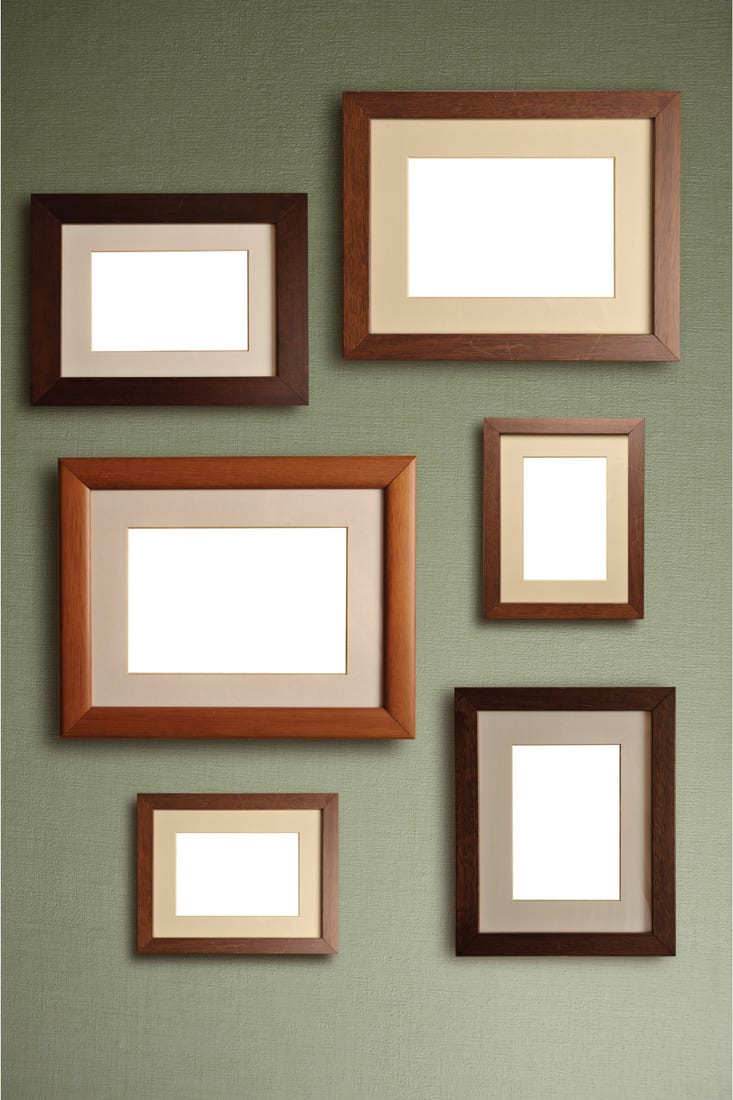 assorted sizes of empty wood frames on a wall