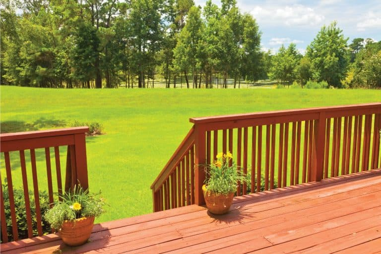 backyard wood deck with wood railing, green backyard, tree line. 11 Incredible Deck Railing Style Ideas